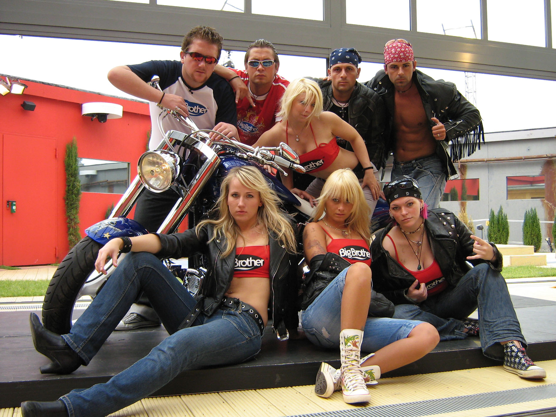 """Bewohner posieren mit dem """"Big Brother Bike"""", einem Unikat aus dem Haus Harley Davidson."""